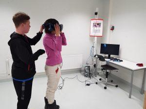 Kuvassa nuori mies auttaa naista sovittamaan VR-laseja päähän.