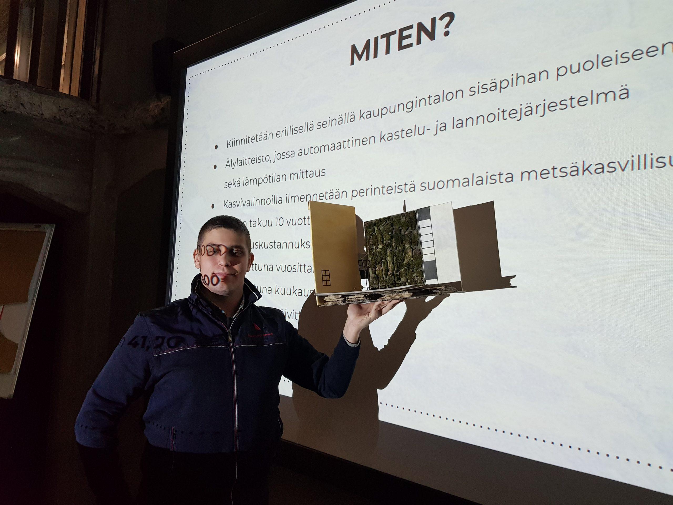 Kuvassa nuori mies esittelee pahvista tilarakennelman prototyyppiä valkokankaan edessä.