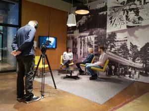 Kuvassa yksi opiskelija kuvaa haastattelutilannetta, jossa haastattelija ja haastateltavat istuvat keskustelemassa sohvaryhmällä.